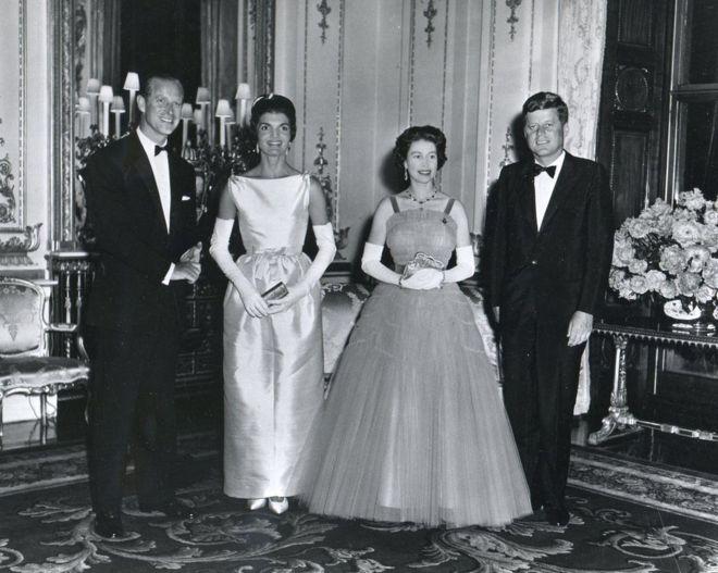 1961年,约翰·肯尼迪总统(右)和他的夫人(左二)(Jacqueline Kennedy)在白金汉宫晚宴上与英国女王和菲利普亲王合影。