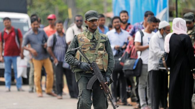 Sri Lankan army personnel stand guard at a checkpoint as they search people and their bags at a check point in Kattankudy near Batticaloa, Sri Lanka, 28 April