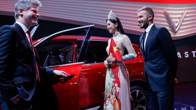 Giám đốc thiết kế của VinFast, Dave Lyon, cùng Hoa hậu Trần Tiểu Vy và cựu danh thủ David Beckham tại lễ ra mắt xe VinFast của Việt nam ở Hội chợ Motor Paris năm 2018 ở Parc des Expositions, Porte de Versailles hôm 02/10/2018