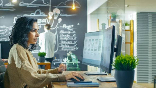 Mulher de blusa em um escritório com um homem ao fundo