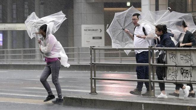 Peatones en Tokio luchan con sus paraguas o sombrillas contra el viento y la lluvia.