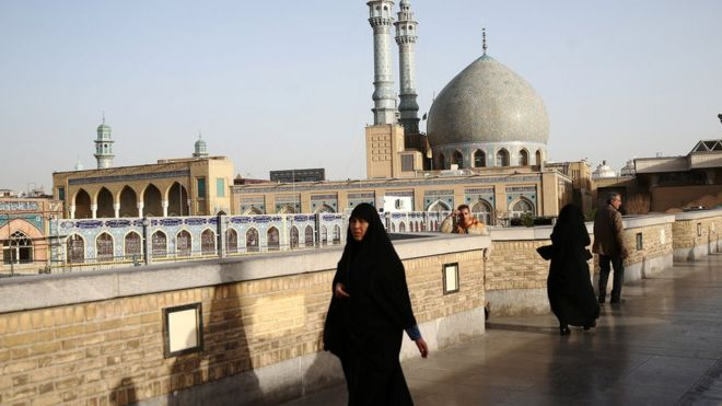 File photo showing people walking past the shrine of Fatima Masumeh in Qom, Iran (9 February 2020)