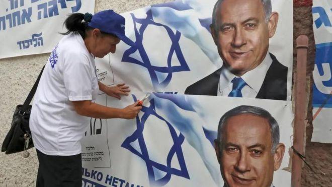 امرأة تعلق لافتة انتخابية لـ نتنياهو