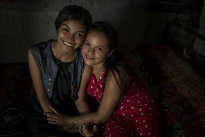 София и Нахан обнимаются, сидя на кровати лачуги, где они живут