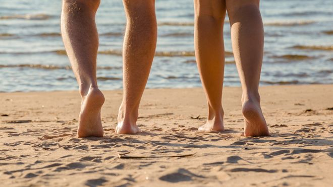 Legs of two people on a beach in Latvia