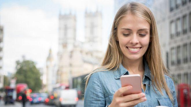Mujer usando celular en las calles de Londres