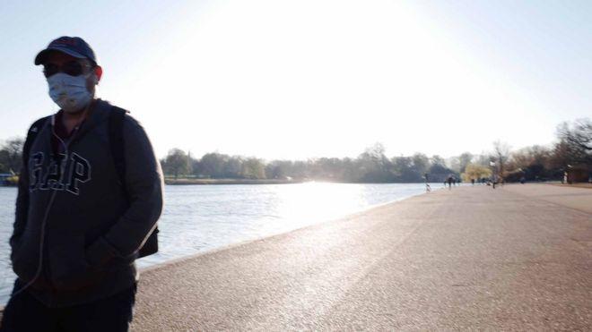 人独自走在伦敦摄政公园池塘旁