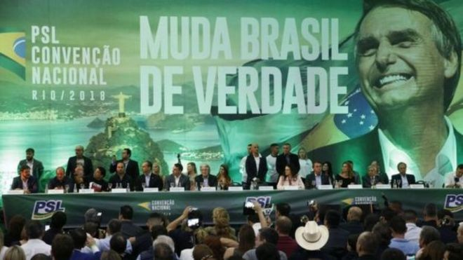 Convenção do PSL tem representantes do partido sentados à mesa sobre palco; no fundo, painel grande com imagem de Bolsonaro e dizeres: 'Muda Brasil de verdade'