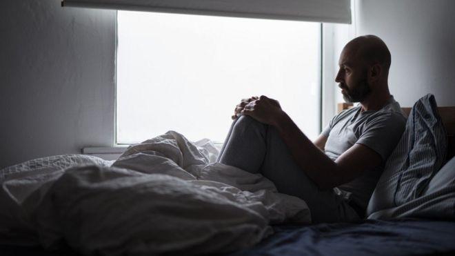 hombre en su cama mira hacia la ventana