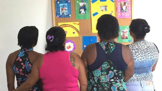 Grupo de mães olha para quadro com fotos de familiares