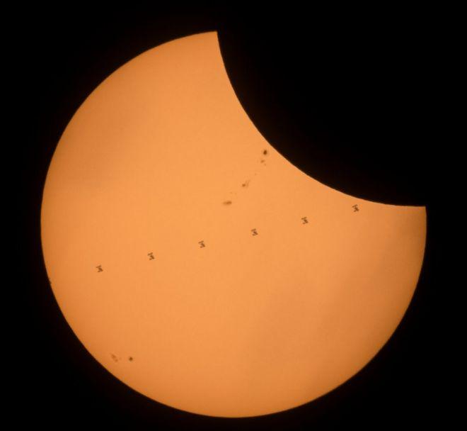 Yedi çerçeveden yapılmış bu kompozit görüntü, 21 Ekim 2017 Pazartesi günü Banner, Wyoming yakınlarındaki kısmi güneş tutulması sırasında saniyede yaklaşık 5 mil / saniye ile Güneş'i geçerken, altı uzayda mürettebat ile Uluslararası Uzay İstasyonunu gösterir. .