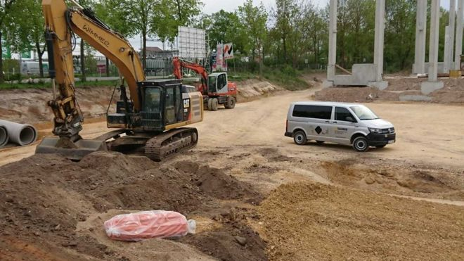 A construction digger is seen, still and vacant, with its digging arm right next to an unexploded bomb wrapped in orange plastic