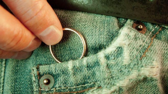 Detalle de jean de hombre con su mano metiendo un anillo al bolsillo