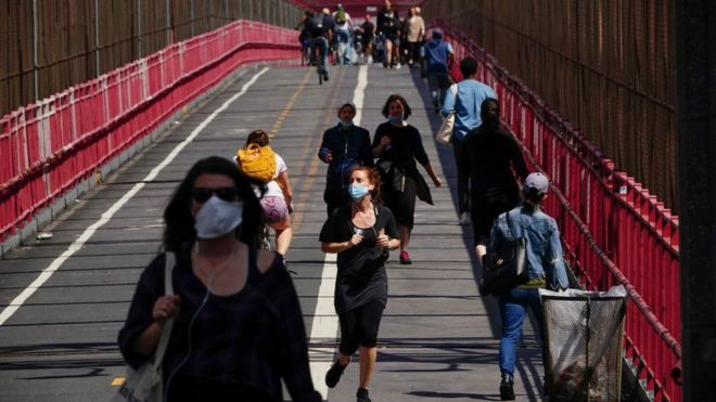 People crossing the Williamsburg bridge in New York wearing face masks