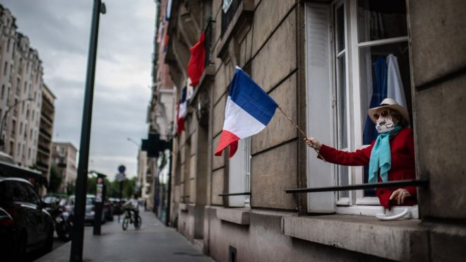 A person in Paris waves the French flag from their window while wearing a protective face covering.