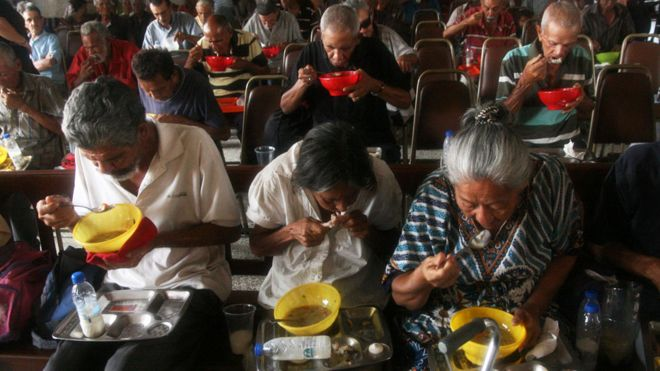 Venezuelans eating food provided by church volunteers