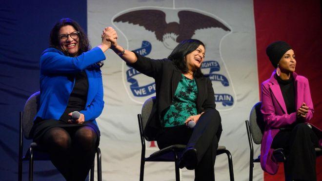 Rashida Tlaib high-fives Pramila Jayapal, while sitting next to Ilhan Omar, on stage at the event in Iowa