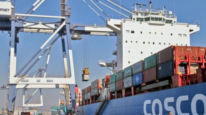 Контейнер выгружается с грузового судна China Ocean Shipping Company (COSCO) в порту в Яньтае, провинция Шаньдун, Китай