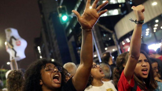 Meninas com os braços levantados e gritando em protesto em rua de São Paulo