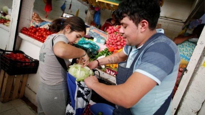 Una mujer embolsa vegetales en Ciudad de México