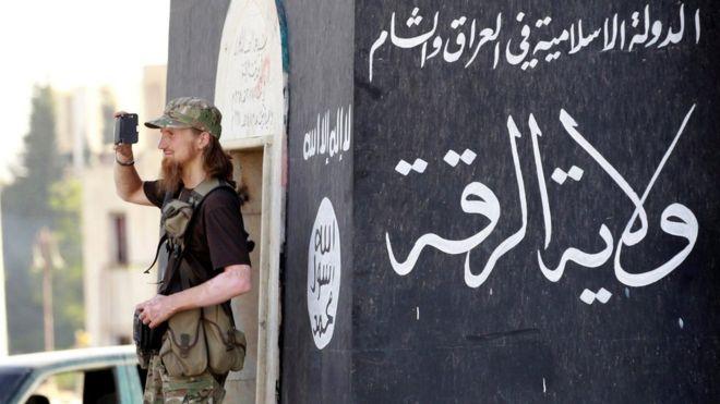Jihadist takes a photo as IS militants celebrate in Raqqa on 30 June 2014
