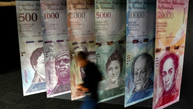 Un hombre pasa delante de unos carteles de los billetes venezolanos.