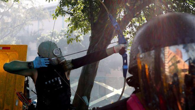 Một người biểu tình dùng cung tên bắn về phía cảnh sát