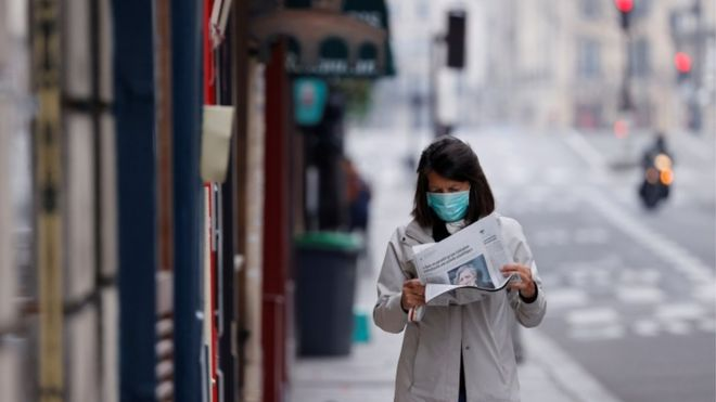 A woman wearing a protective face mask reads a newspaper as she walks in a street on the deserted Ile Saint Louis in Paris