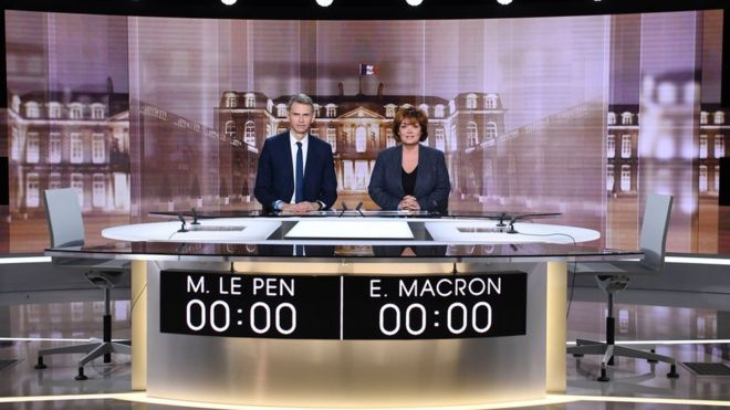 French journalists and TV hosts Christophe Jakubyszyn (L) and Nathalie Saint-Cricq pose on the TV set installed in a studio on May 2, 2017 in La Plaine Saint Denis