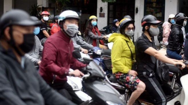 Luz verde para la vuelta a la normalidad: ciudadanos de Hanoi esperan en sus motonetas el cambio de luz.