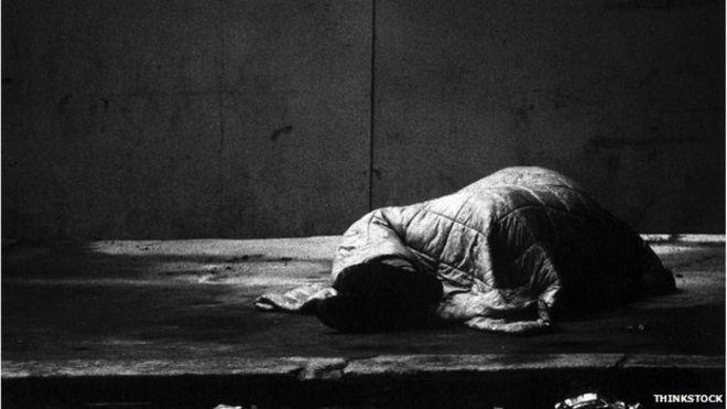Спит грубо - человек, спрятанный на улице спальным мешком в черно-белом изображении