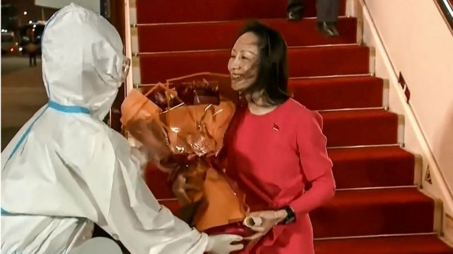 This screen grab made from video released by Chinese state broadcaster CCTV shows Huawei executive Meng Wanzhou receiving flowers after she arrived following her release