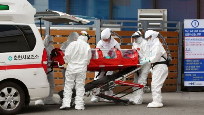 Medical workers wearing protective gear carry a patient infected with the Covid-19 coronavirus at a hospital in Chuncheon on February 22, 2020