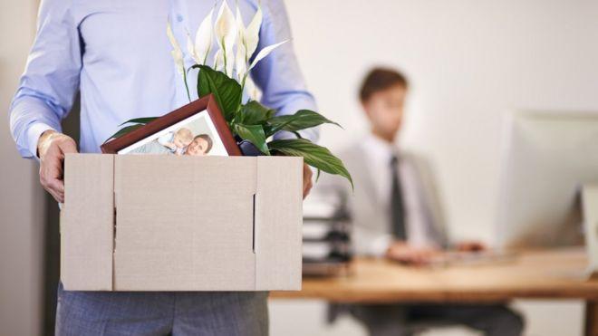 Homem se demitiu e carrega caixa com seus pertences