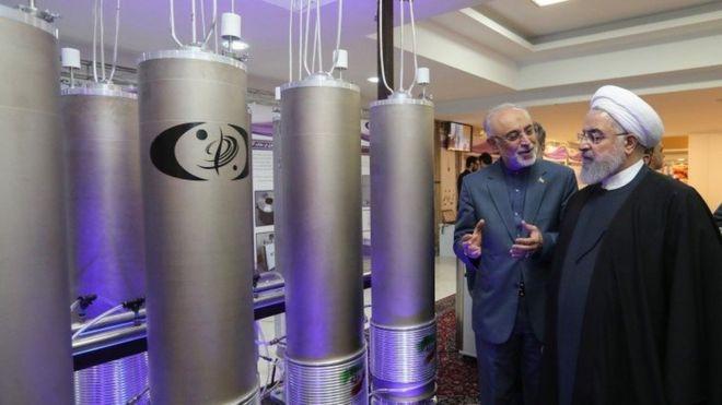 """El presidente iraní Hassan Rouhani (derecha) escucha al jefe de la organización de tecnología nuclear de Irán, Ali Akbar Salehi, durante el """"día de la tecnología nuclear"""" en Teherán."""