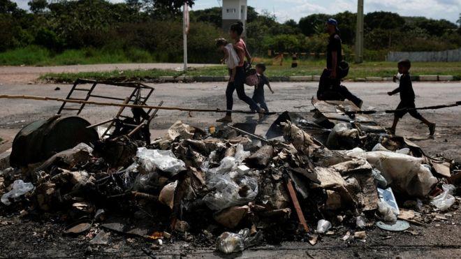Venezuelanos diante de tendas queimadas em protesto no sábado