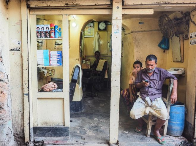 Bangladesh, 2014. Men sit in a hair salon.