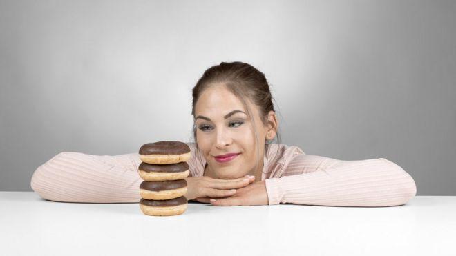 Mujer mirando una torre de donuts.