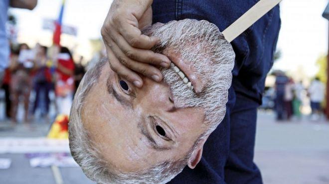 Brasileiro segura máscara de Lula na porta da ONU na Suíça em 15 de agosto de 2018