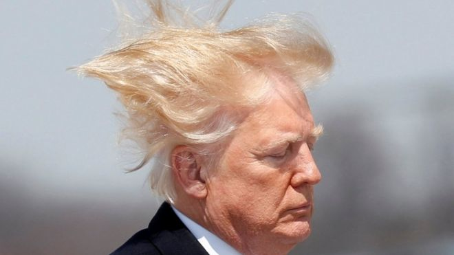 US President Donald Trump boards Air Force One on a windy day in Maryland in 2018