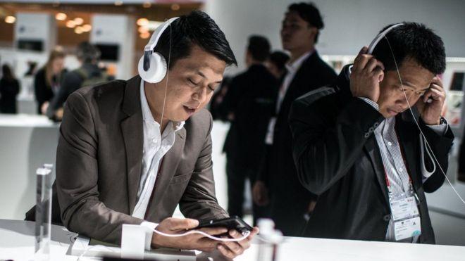 ผู้ชายกำลังฟังเพลงด้วยหูฟัง