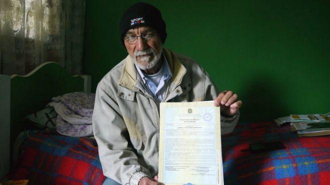 Leonardo da Cruz, pai de Robson, sentado em sua cama, mostra a certidão de óbito do filho, com o nome 'desaparecido'