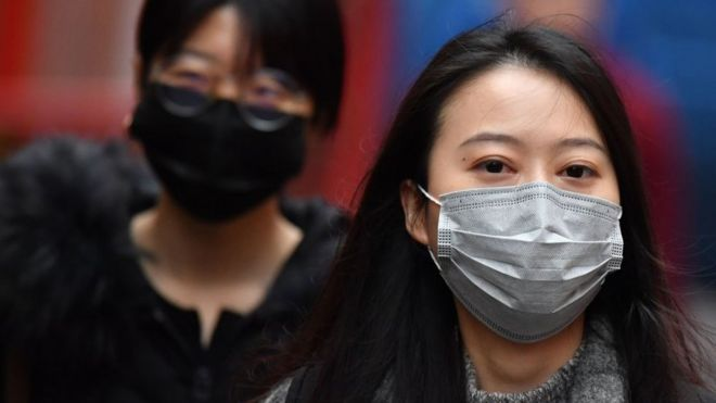 Pedestrians wear surgical masks in London's China Town on January 24, 2020
