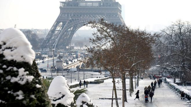People walk on the snow-covered Trocadero gardens near the Eiffel Tower in Paris, as winter weather with snow and freezing temperatures arrive in France, February 8, 2018