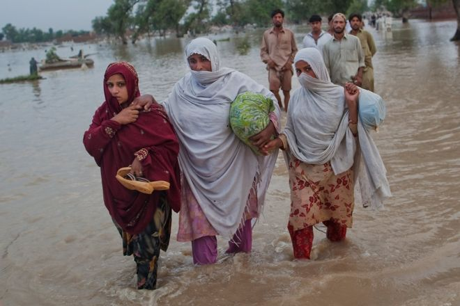 Three women in Pakistan wade through floodwater, carrying their belongings