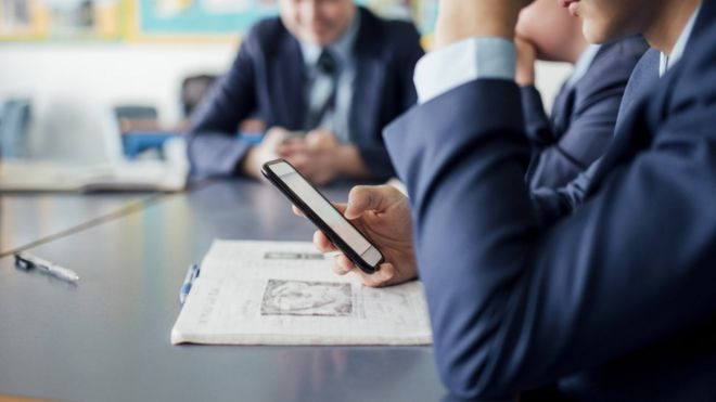 A school pupil in uniform using a smartphone at their desk