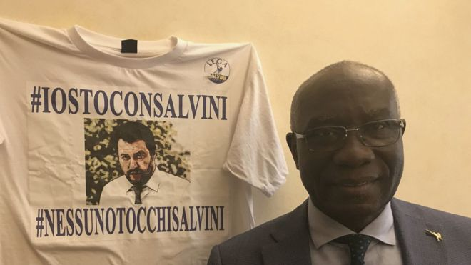 Tony Iwobi standing next to a Salvini t-shirt