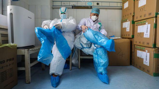 เจ้าหน้าที่การแพทย์ 2 คน กำลังสวมชุดป้องกันที่โรงพยาบาล เพื่อรักษาคนไข้ติดเชื้อไวรัสโคโรนาในเมืองอู่ฮั่น ประเทศจีน