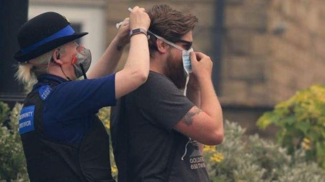 Сотрудник общественной полиции помогает человеку надеть маску от пыли