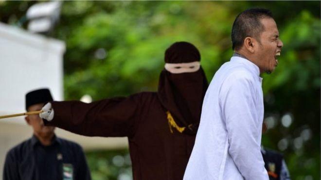 Mukhlis, membre du Conseil des oulémas d'Aceh (MPU), réagit lorsqu'il est puni en public.